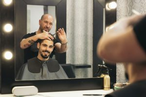 Hairstylist making men's grooming haircut to an attractive man.