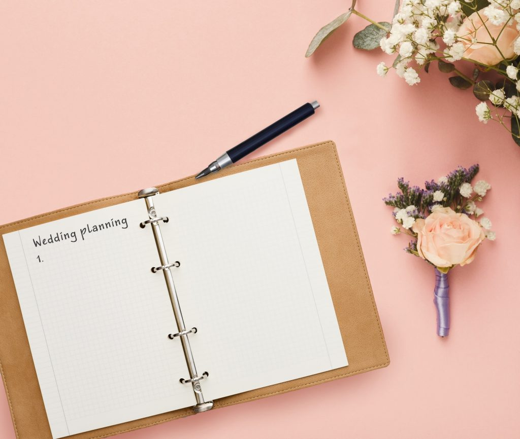 Notepad with wedding planning checklist and bridal flower bouquet composition, creative background