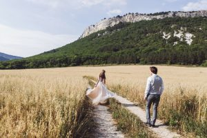 Photo shoot bride and groom in a beautiful wheat field surrounded by mountains