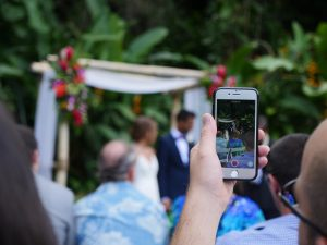 Hand recording video of a wedding on a cellphone