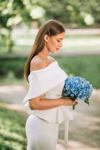Sad Bride Looking At Bouquet Standing Alone In Park, Vertical